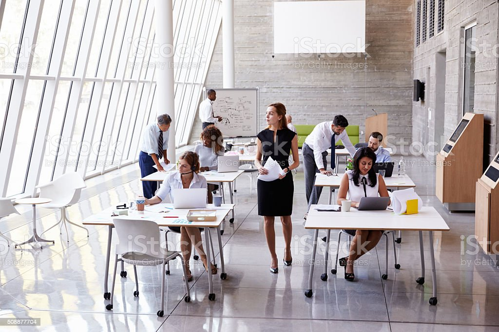 Overhead View Of Businesspeople Working At Desks In Office stock photo