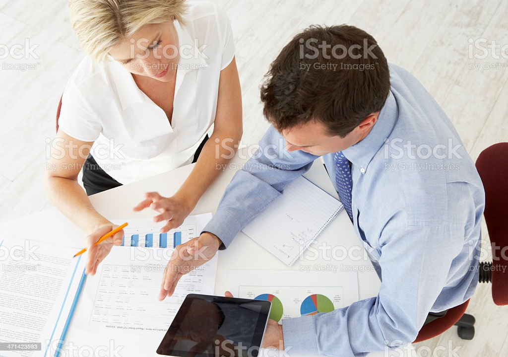 Overhead View Of Businesswoman And Businessman Working At Desk royalty-free stock photo