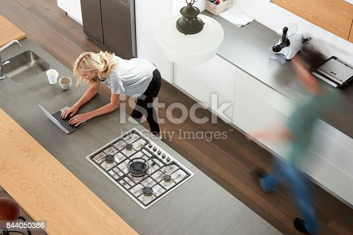 844050630 istock photo Overhead View Of Busy Couple In Modern Kitchen 844050386
