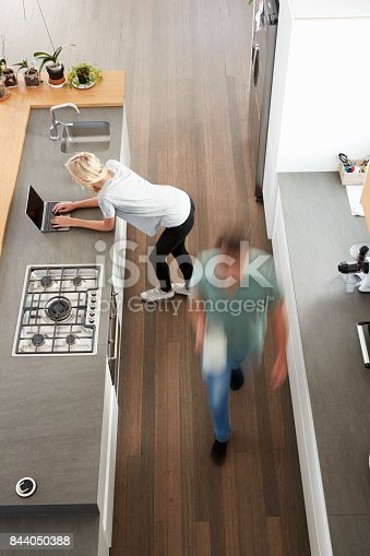 844050630 istock photo Overhead View Of Busy Couple In Modern Kitchen 844050388