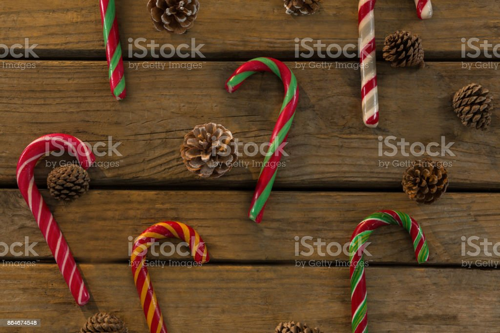 Overhead view of candy canes and pine cones on table stock photo