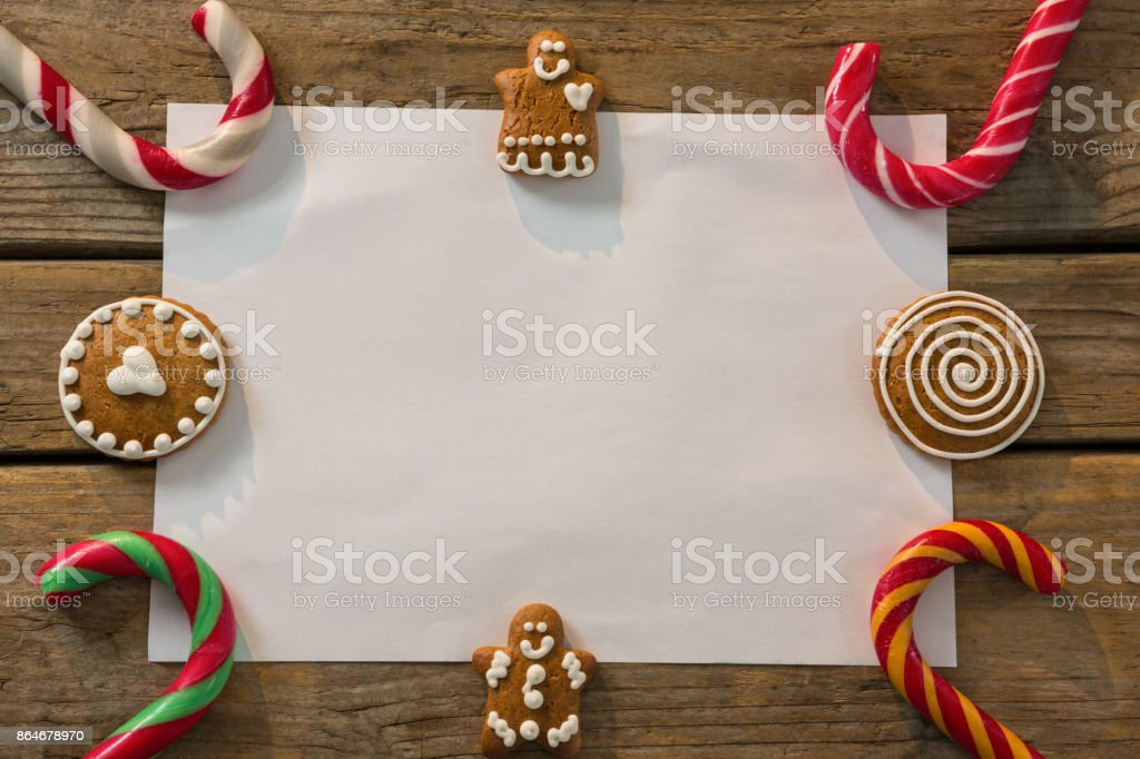 Overhead view of candy canes with gingerbread cookies and paper arranged on table stock photo
