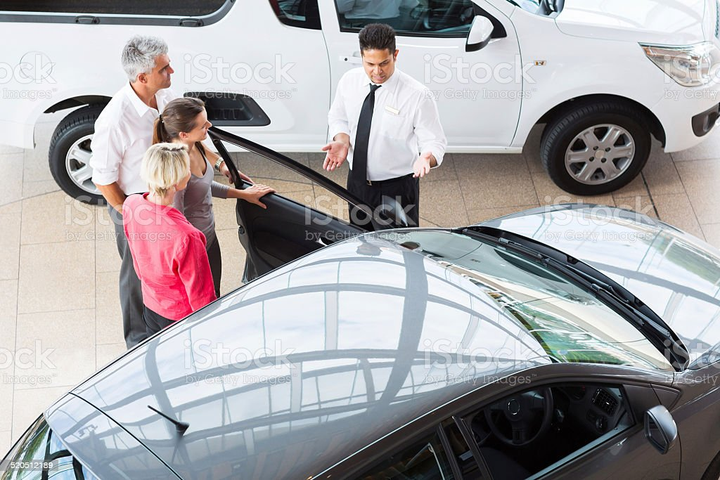 overhead view of car salesman showing vehicle to customers stock photo
