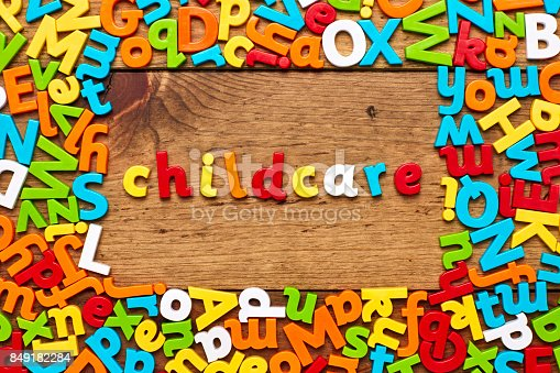849191694 istock photo Overhead view of childcare surrounded with colorful alphabets on wood 849182284
