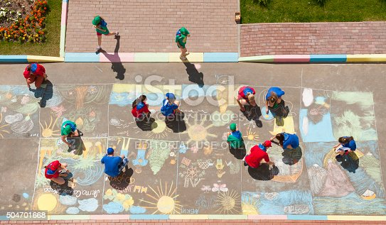 istock Overhead view of children drawing chalk pictures 504701668