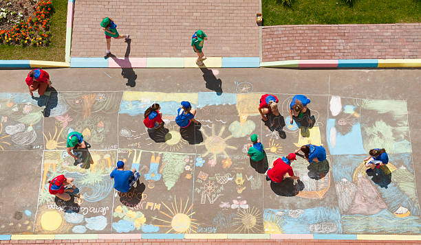 overhead view of children drawing chalk pictures - chalk drawing stock photos and pictures