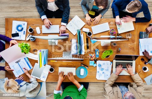 istock Overhead view of colleagues at work on one table 496854935