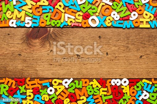 849181972istockphoto Overhead view of colorful alphabets and numbers arranged on wood 849182490
