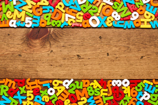 Overhead view of colorful alphabets and numbers arranged on wood stock photo