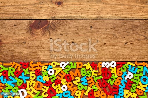 849191694 istock photo Overhead view of colorful alphabets and numbers arranged on wood 849182536