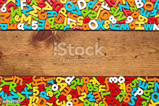 849191694 istock photo Overhead view of colorful alphabets and numbers arranged on wood 849191762