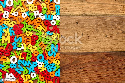 849191694 istock photo Overhead view of colorful alphabets and numbers arranged on wood 849192208