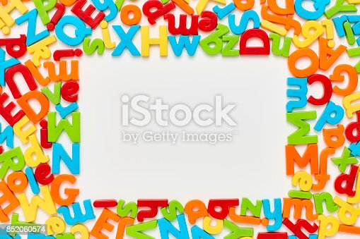 istock Overhead view of colorful alphabets in frame on white background 852060574