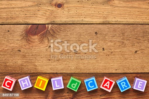 istock Overhead view of colorful childcare blocks arranged on wood background 849187158