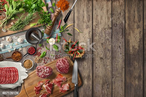 istock Overhead view of colorful roast vegetables, savory sauces and salt served with grilled t-bone steak on a rustic wooden counter in a country steakhouse 657126126
