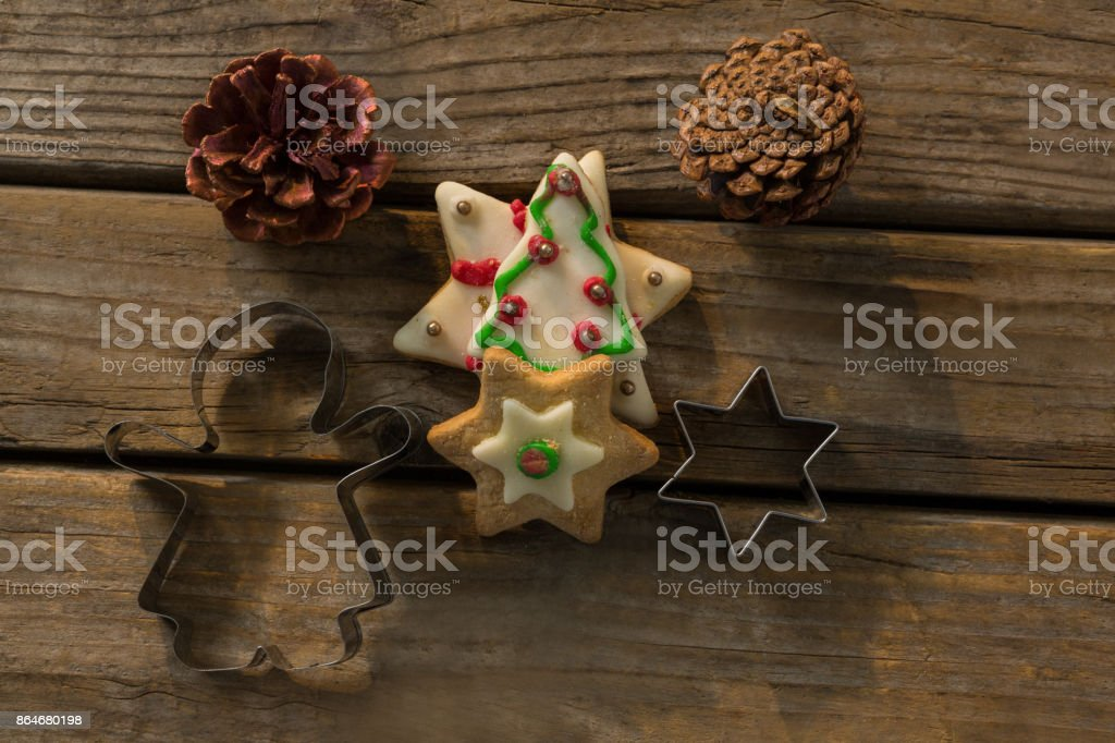 Overhead view of cookies with pine cones and pastry cutters on table stock photo