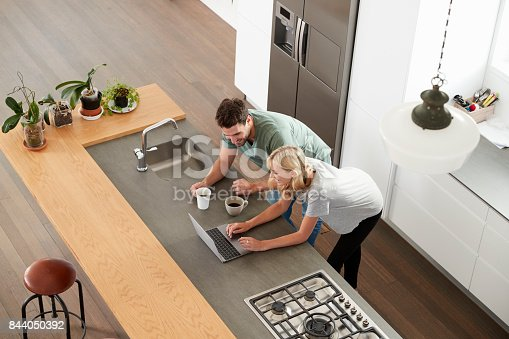 844050630 istock photo Overhead View Of Couple Looking At Laptop In Modern Kitchen 844050392