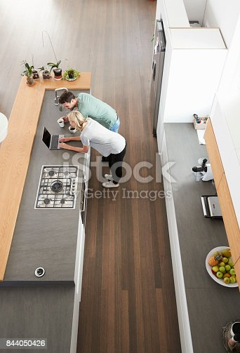 844050630 istock photo Overhead View Of Couple Looking At Laptop In Modern Kitchen 844050426