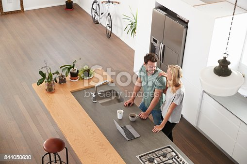 istock Overhead View Of Couple Looking At Laptop In Modern Kitchen 844050630