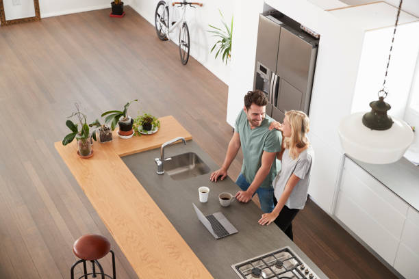 Overhead View Of Couple Looking At Laptop In Modern Kitchen stock photo