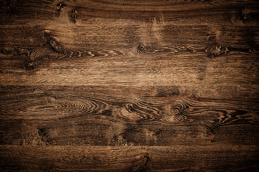 Overhead view of dark brown floor texture. A wood background with multiple planks placed close together.  The planks feature a variety of light and dark brown shades.  The darkest shades are on the corners, the lightest on the middle. There are variety of knots and swirls on it.