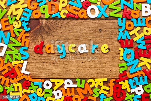 849191694 istock photo Overhead view of daycare surrounded with colorful alphabets on wood 849188142