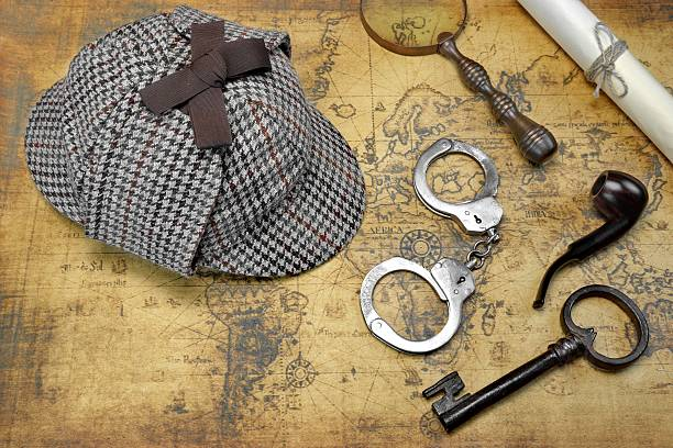 Overhead View Of Deerstalker Hat And Detective Tools On Map Overhead View Of Sherlock Holmes Deerstalker Hat  And Private Detective Tools On The Old World Map Background. Items Include Vintage Magnifying Glass, Retro Key, Manuscript, Smoking Pipe,  And Handcuffs deerstalker hat stock pictures, royalty-free photos & images