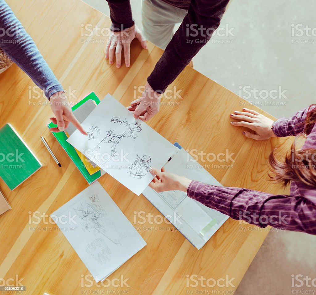Overhead view of designers collaborating at table in studio stock photo