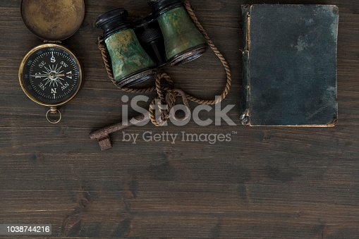 Top view of wooden table with old needle compass, binoculars, rusted key and captain's diary.
