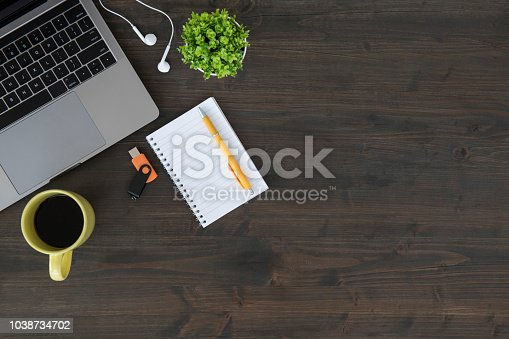 Top view of wooden table with laptop, plant, headphones, coffee cup, note pad with pencil and USB device.