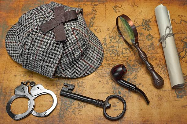 Overhead View Of Detective Deerstalker Hat And Tools On Map Overhead View Of Sherlock Holmes Deerstalker Hat  And Private Detective Tools On The Old World Map Background. Items Include Vintage Magnifying Glass, Retro Key, Manuscript, Smoking Pipe,  And Handcuffs sherlock holmes stock pictures, royalty-free photos & images
