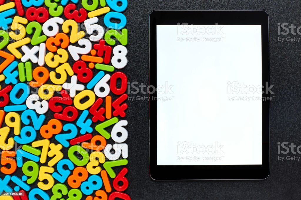 Overhead view of digital tablet by mathematical objects on blackboard stock photo
