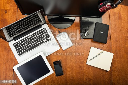 Chatham, Canada - May 22, 2014: Overhead view of a students desk. On top of the desk is an assortment of popular electronics devices. These include Apple products, iMac, laptop, iPhone, and iPad. There is an e-reader, notepad and pen. Back to school concept. There are no people in the image.