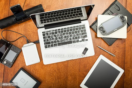 Chatham, Canada - May 22, 2014: Overhead view of a students desk. On top of the desk is an assortment of popular electronics devices. These include Apple products,  laptop, iPhone, and iPad. There is a Playstation portable hand-held game. Also included is a Wacom drawing tablet and a hard drive. Back to school concept. There are no people in the image.