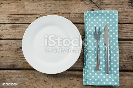 istock Overhead view of empty plate by napkin and eating utensils 825803570