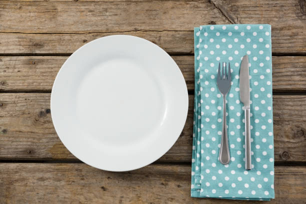 overhead view of empty plate by napkin and eating utensils - blue table setting stock photos and pictures