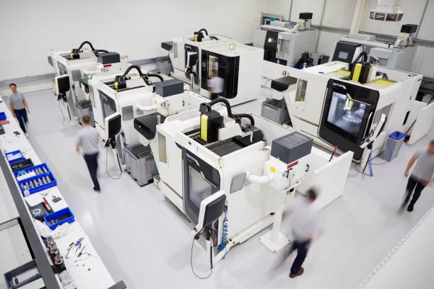 bovenaanzicht van engineering workshop met werknemers die gebruikmaken van de cnc machines - cnc machine stockfoto's en -beelden