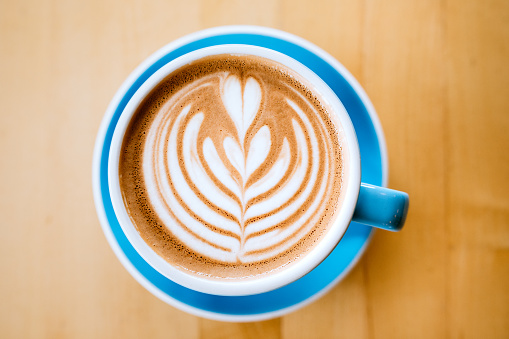 A freshly poured latte, with a heart floral pattern created in the coffee drink.