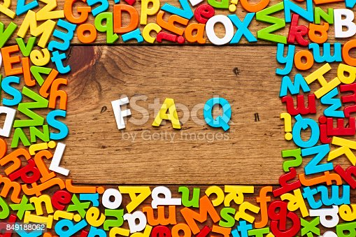 849191694 istock photo Overhead view of FAQ surrounded with colorful alphabets on wood 849188062
