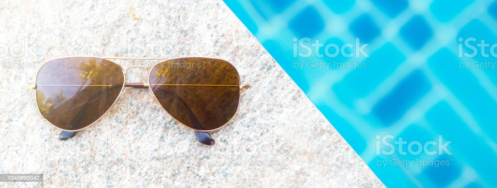 Overhead view of fashion sunglasses and poolside. Summer holiday...