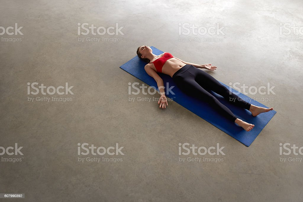 Overhead view of fit young female relaxing on yoga mat. stock photo