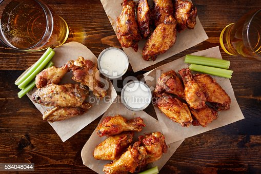 istock overhead view of four different flavored chicken wings with beer 534048044