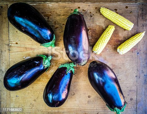 High angle color image depictina an arrangement of fresh aubergines and corncobs on a weathered wooden surface. Room for copy space.