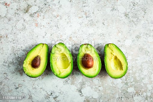 Color image depicting an overhead view of fresh avocados. The avocados have been cut in half and are presented on rustic surfaces with plenty of room for copy space.