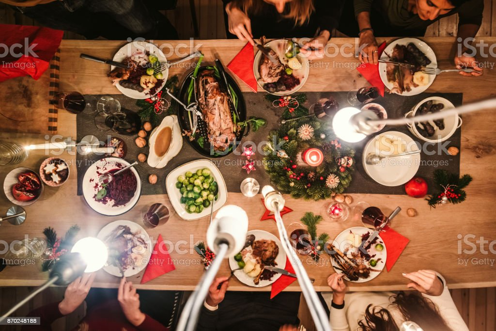 overhead view of friends at table during christmas dinner stock