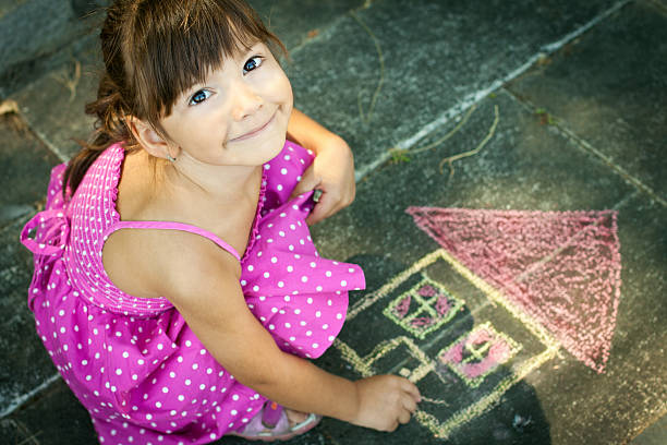 Overhead view of girl drawing on the sidewalk Beautiful Little girl drawing her dream house chalk drawing stock pictures, royalty-free photos & images