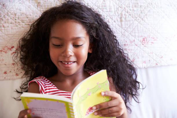 bovenaanzicht van meisje liggend op bed en het lezen boek - a little girl reading a book stockfoto's en -beelden