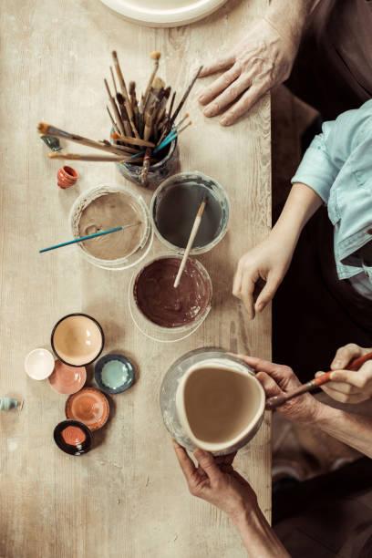 draufsicht der mädchen malerei tontopf und großeltern helfen beim workshop - handbemalte teller stock-fotos und bilder
