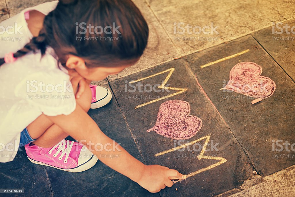 Overhead view of girl writing on the sidewalk stock photo