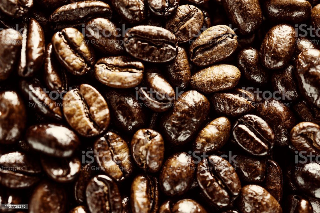Overhead view of Glossy golden roasted Coffee beans. stock photo